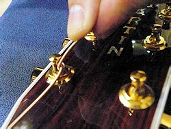 使多余部分的弦朝上一点,这样做在下一步紧弦时,多余的弦就不会卡在其他地方。